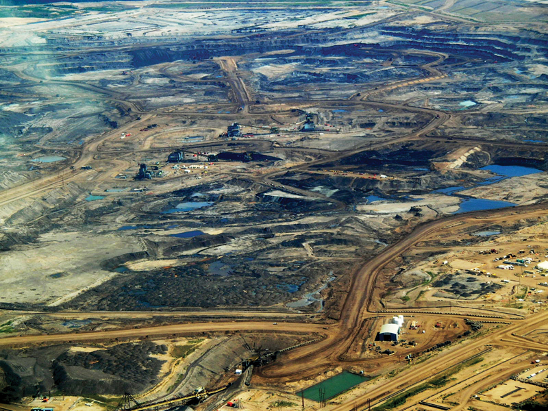 "Open-pit mining of oil sand in Alberta, Canada. The ponds in the photo are ""tailings ponds"", containing a mixture of water, fine sand, clay, and residual oil components after the sands have been processed to remove most of the oil."