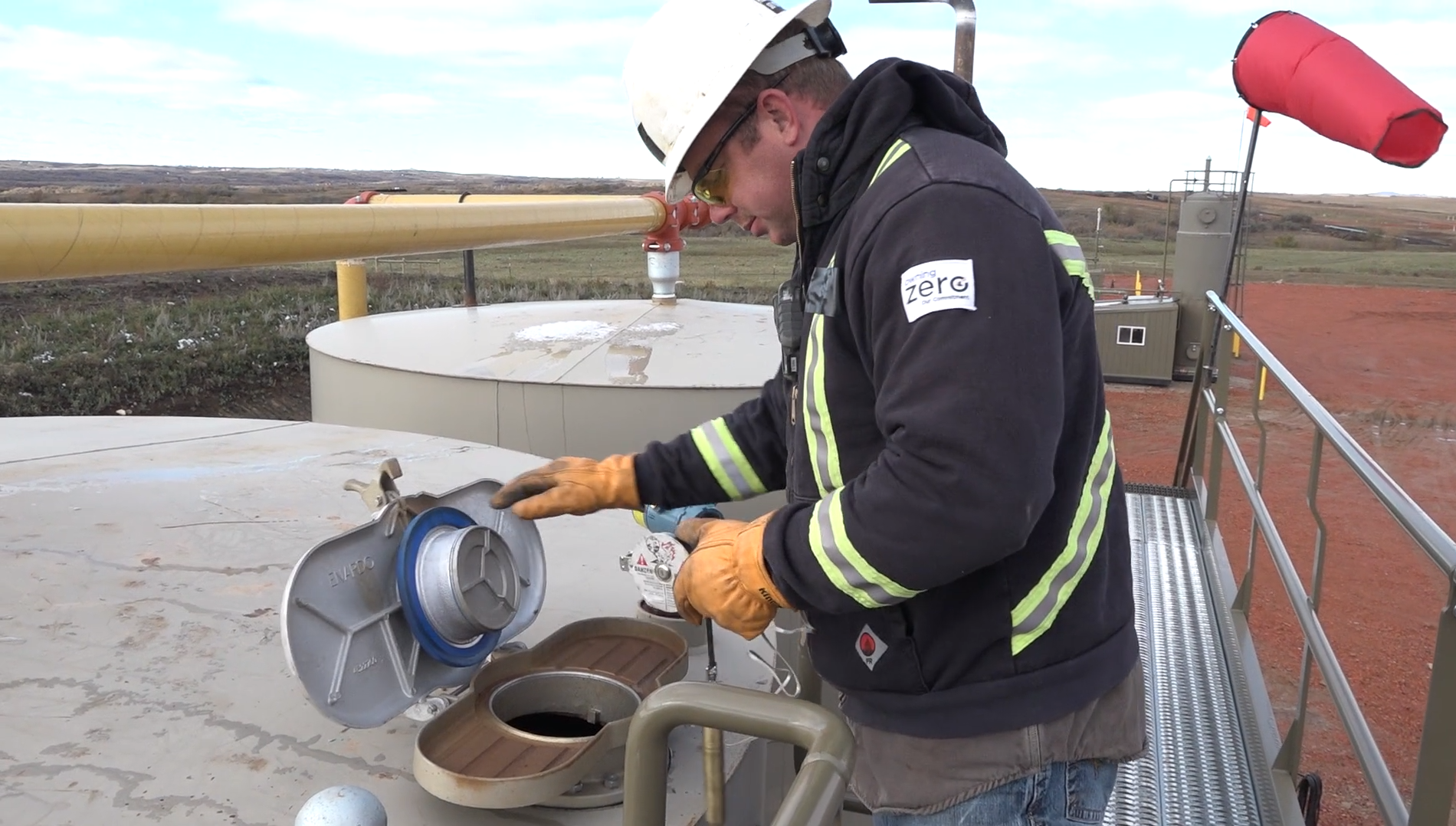 Worker gauging an oilfield tank. Tank sampling is one of the main ways in which oilfield workers may be exposed to harmful vapors.