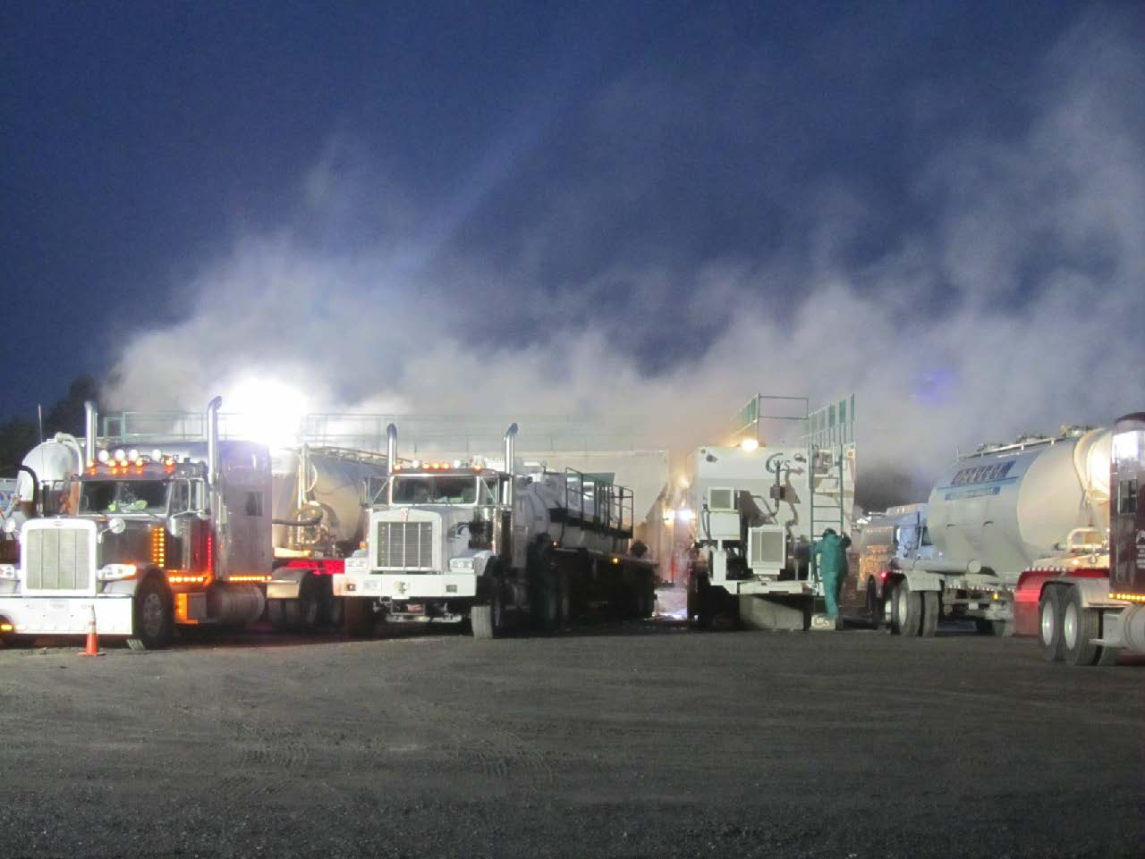 Silica dust clouds from delivery trucks loading into sand movers at a hydraulic fracturing site. Inhalation of this silica is a major hazard associated with oil and gas operations.