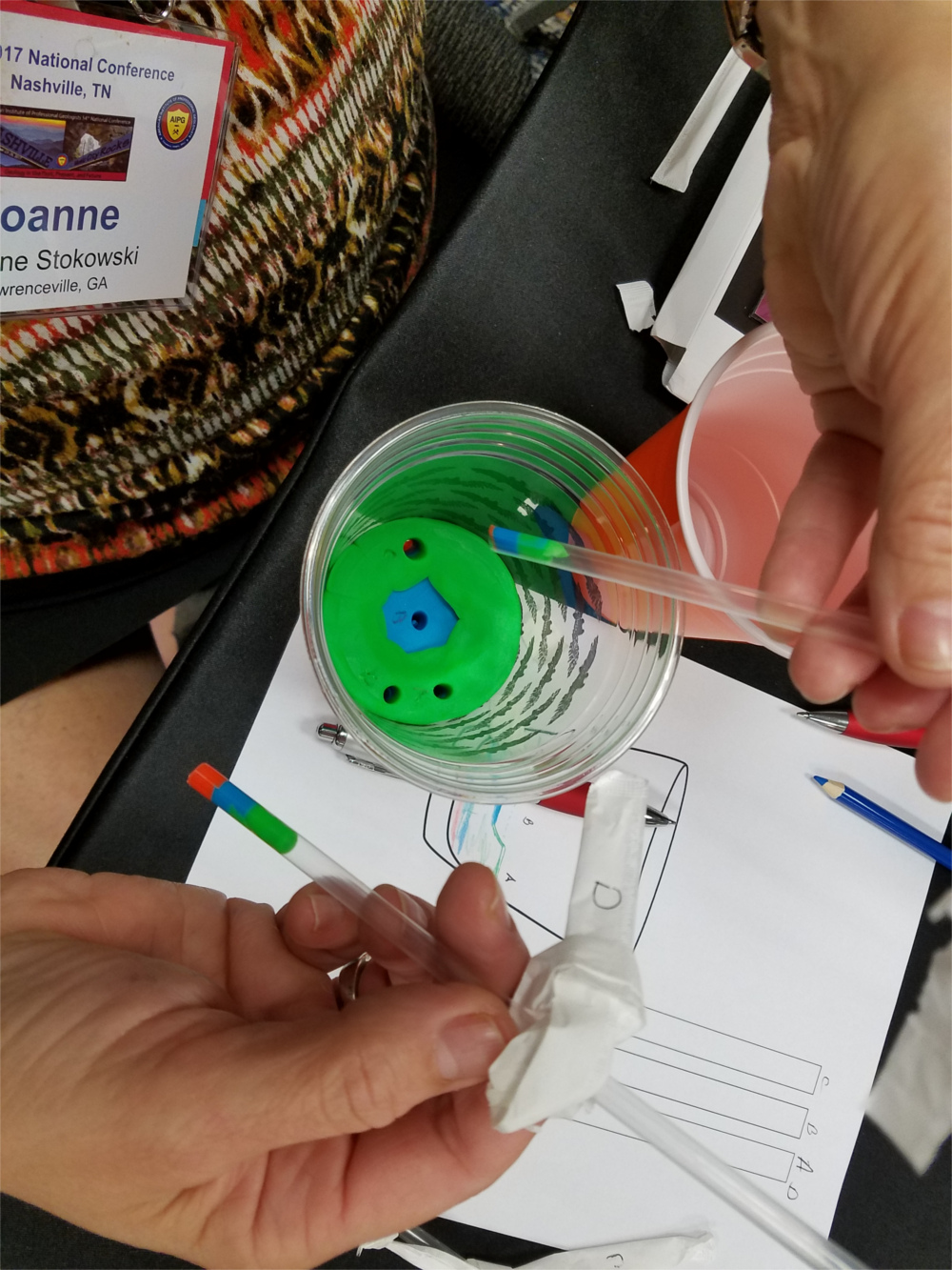 Top view of a cup with green and blue play-doh in it. Two straws have punctured the cup, and are showing different distributions of the playd-oh depending on where the sampling was done.