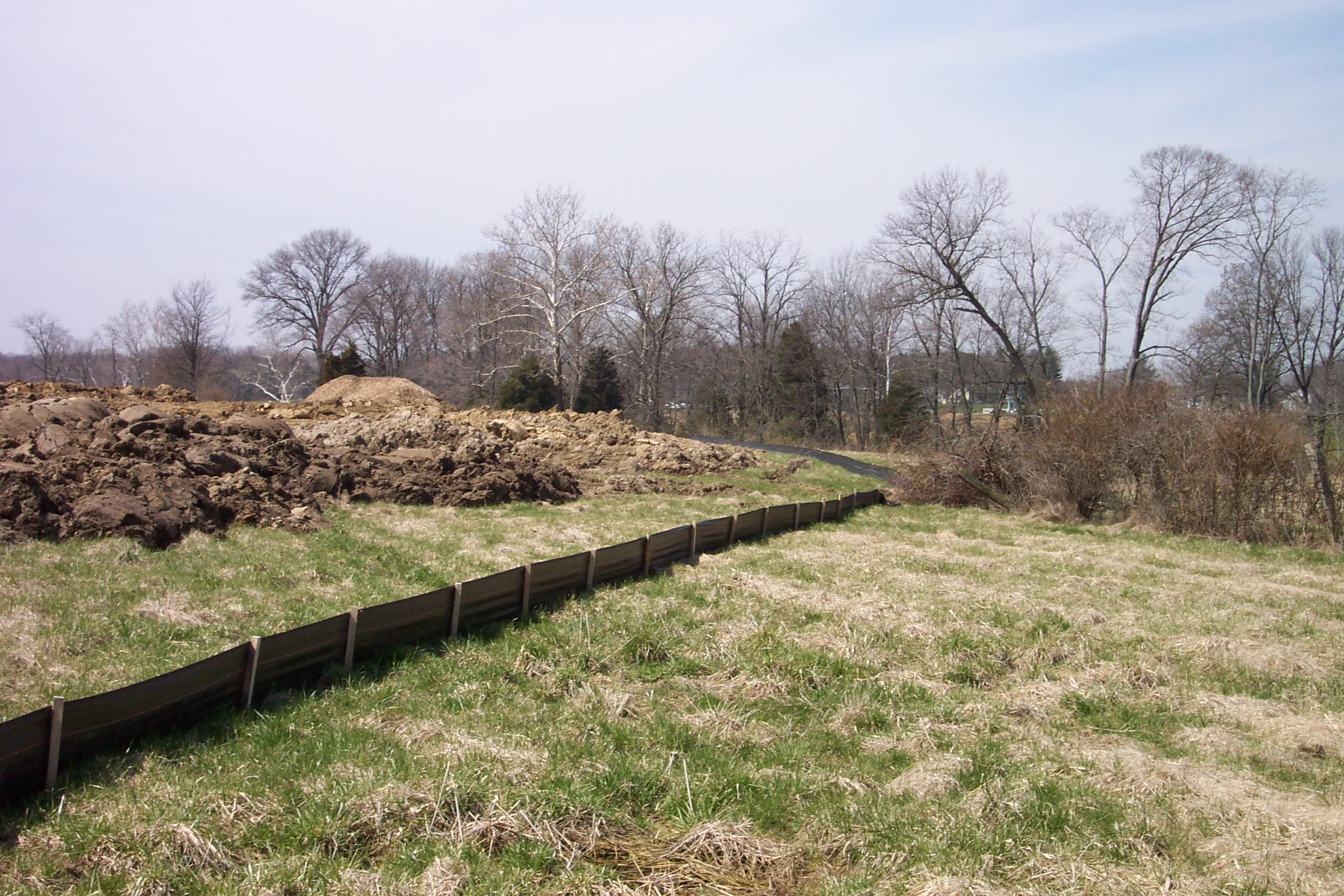 Plastic fencing to control soil erosion and stormwater runoff at a construction site.