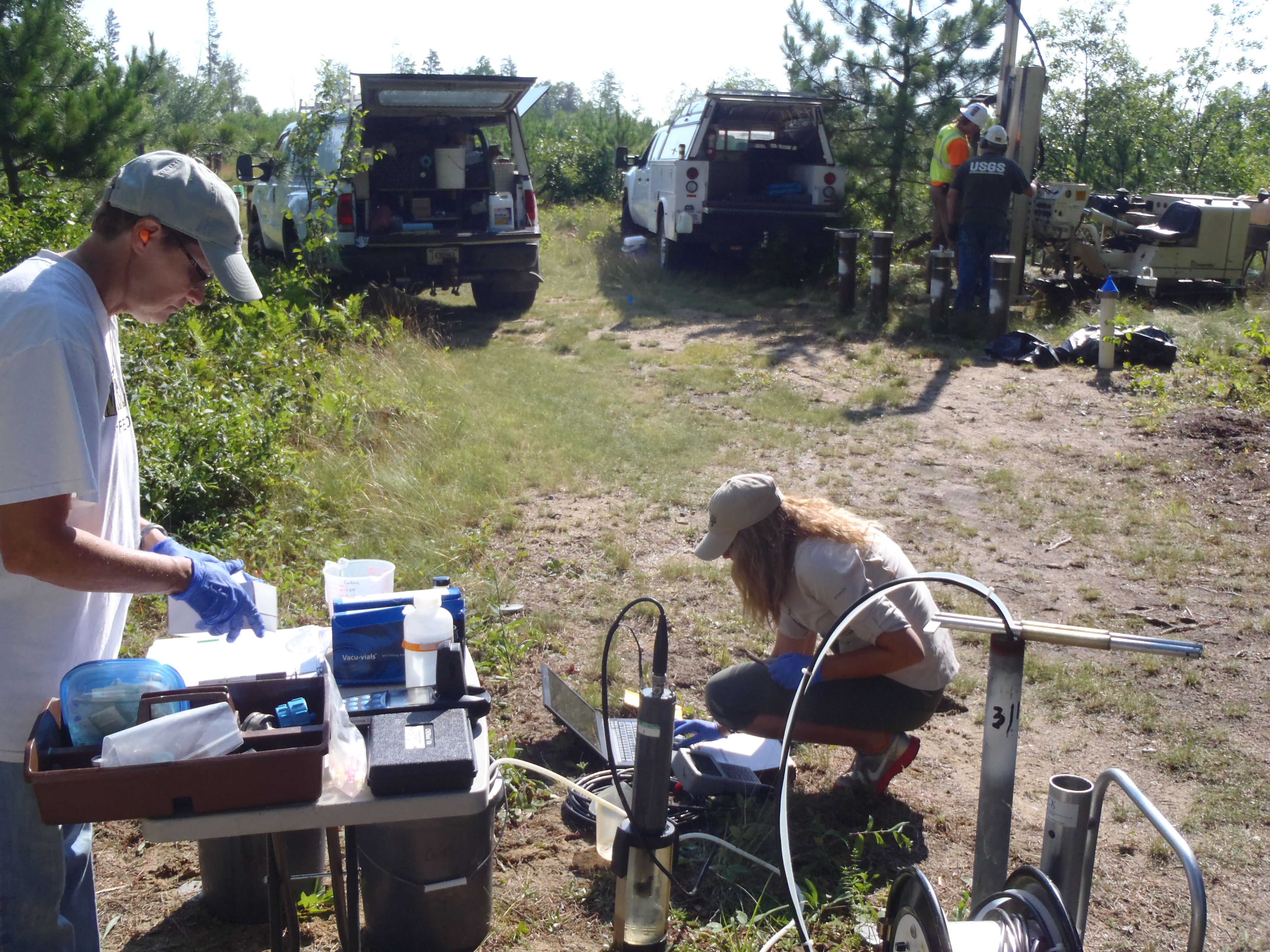 USGS scientists collecting a groundwater sample from a well to monitor how the different components of crude oil that has contaminated groundwater are broken down over time by biological activity.