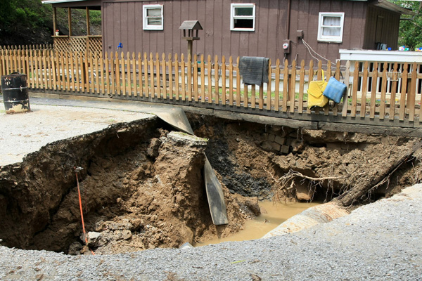 A sinkhole in front of a home in Kentucky. Image Credit: FEMA/Photo by Rob Melendez