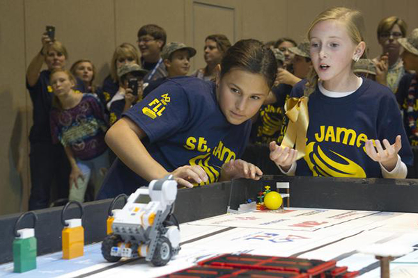 Two students anxiously watch their robot during the 2012 FIRST LEGO League Mississippi Championship Tournament in Hattiesburg, Miss., on Dec. 1. (Credit: NASA/SSC)