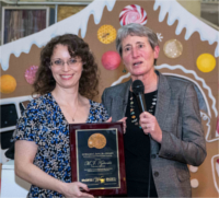 Mary Tykoski smiling, receiving the Ed Roy award from Sally Jewell, who is holding a microphone and speaking to an unseen crowd.