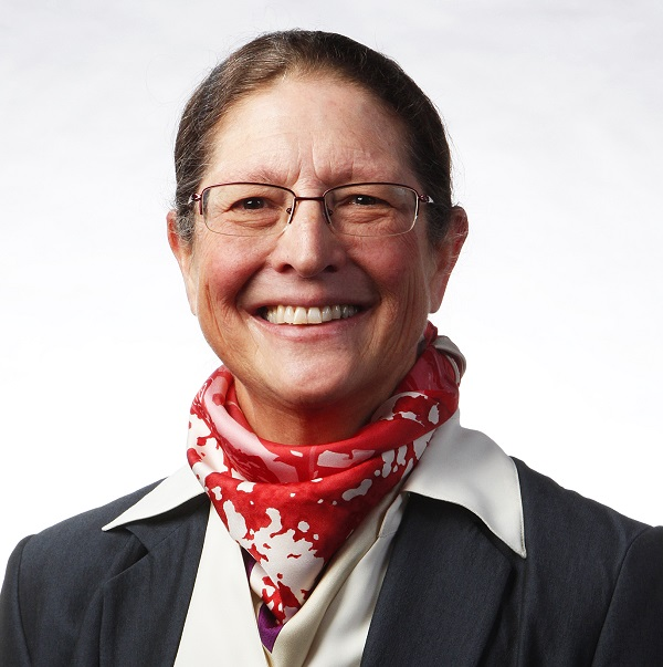 Eve Sprunt. Woman Smiling with a red and white scarf and glasses.