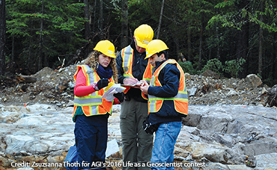 Scientists wearing safety vests and helmets look at their notes in front of a rocky forested backdrop.