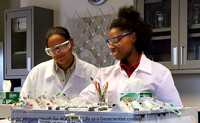 Two young scientists working in a lab. One wears a big smile as she shows something to her colleague.