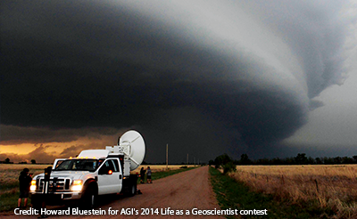 Scientists stand by a truck with weather monitoring equipment with a large stormcloud overhead