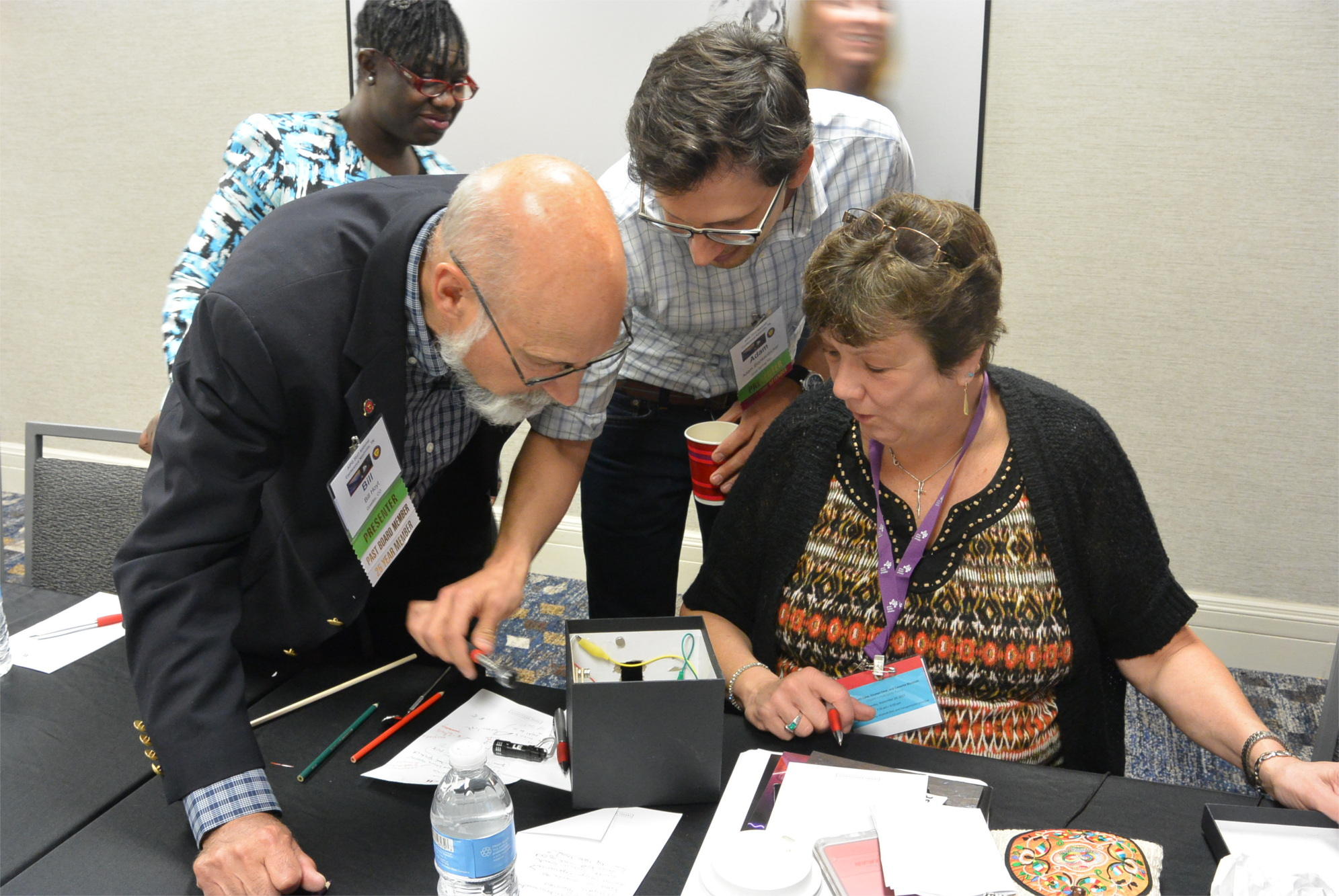 Three people looking into a small box. A few wires are exposed from the box. One person is holding a light near the box.