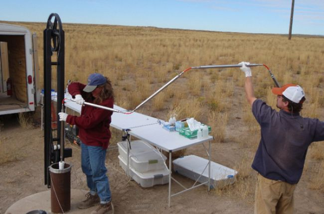 USGS scientists deploying specialized water-sampling bottles into a well equipped with a multilevel monitoring system at the Idaho National Laboratory, Idaho. Image Credit: U.S. Geological Survey Idaho National Laboratory Project Office.