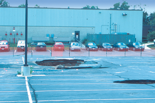 Fig. 1. Sinkholes in collapsed parking area, Frederick, MD. Sinkholes form in carbonate areas as the dissolving and weakening of bedrock cause it to collapse. Credit: D.K. Brezinksi
