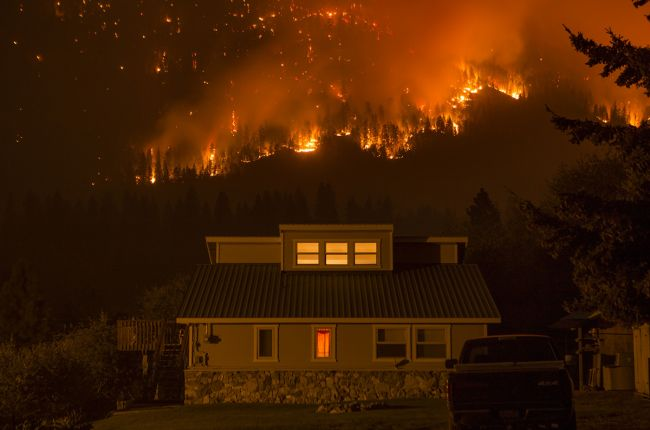 Wildfire burns on a mountain behind a house, First Creek Fire, Washington. Image Credit: U.S. Forest Service
