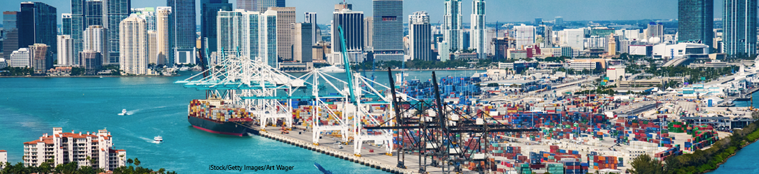 An aerial view of the Port of Miami. The foreground has blue water with several recreational boats, vacation condo buildings with beaches, fuel storage tanks and a shipyard with cranes and a cargo ship. Background shows many skyscrapers.