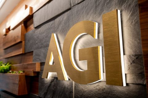 AGI in backlit gold lettering against a slate and wood backdrop.