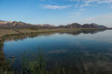 A clear pond with grass in the foreground, a pipe in the mid-ground, and mountains in the background. The sky is blue with wisps of clouds