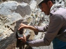 A geologist taking measurements of an outcrop to create a geologic map