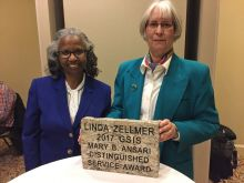 Linda Zellmer (right) and Clara McLeod, stand next to each other in front of a granite rock plaque with *Linda Zellmer 2017 GSIS Mary B. Ansari Distinguished Service Award* carved into it.