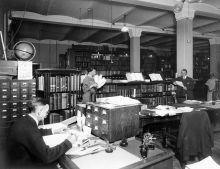 U.S. Geological Survey library in Hooe Building, Washington DC. Note rotating bookcase at left, next to card catalogs, left to right: J.M. Nickles, J.L.V. McCord original Survey librarian, J.E. Latimer, and Mary Coats. 1917.