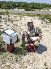 GIP participant, Ruth Coffey, wearing a bug-suit for mosquito protection and using an electric tape to measure depth to groundwater in a well at Assateague Island National Seashore